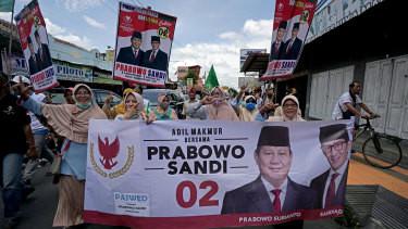 Supporters gesture as they carry a banner featuring Prabowo Subianto, presidential candidate, left, and Sandiaga Uno, vice-presidential candidate, during a campaign in Klaten, Yogyakarta, Indonesia, on  March 23.