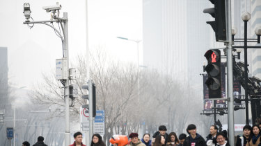 Pedestrians wait to cross a road as surveillance cameras operate in Tianjin, China.