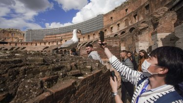 A tourist wearing a mask takes a photo at the Colosseum in Rome on Saturday.