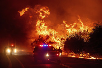 Flames lick above vehicles on Highway 162 as the Bear Fire burns in Oroville, California.