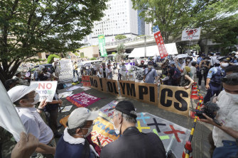 Anti-Olympics protesters hold signs during a rally near the Tokyo Metropolitan Government complex where the final Olympic torch relay event took place in Tokyo on Friday.