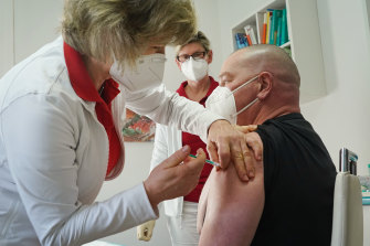 Dr Claudia Richartz inoculates a healthcare worker against COVID-19 in Brandenburg, Germany.
