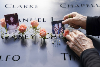 Mourners place flowers and pictures on the September 11 memorial in New York City.