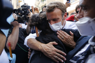 French President Emmanuel Macron hugs a resident during a visit to Beirut on Thursday.