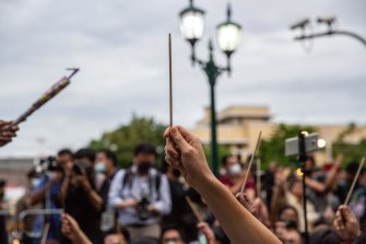"Anti-government protesters wave chopsticks as makeshift wands to ""Cast the Patronus Charm to Protect Democracy"" in Bangkok on Monday."