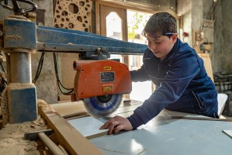 Mahmoud, 13, works as a carpenter. With three years' experience, he now manages the electric saw.