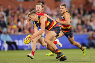 Nick Murray of the Crows handballs in the final seconds of Adelaide's round 10 match against the Demons.