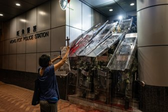 A woman holds a cross in front of the Mongkok Police Station as riot police holding shields stand guard during a standoff with protesters after an anti-government rally in on September 1, 2019 in Hong Kong.