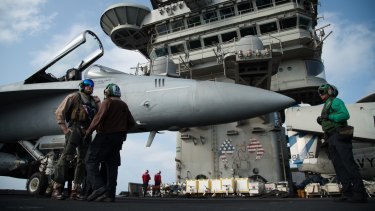 A pilot speaks to a crew member by an F/A-18 fighter jet on the deck of the USS Abraham Lincoln aircraft carrier in the Arabian Sea. Donald Trump has threatened Iran with 'obliteration'.