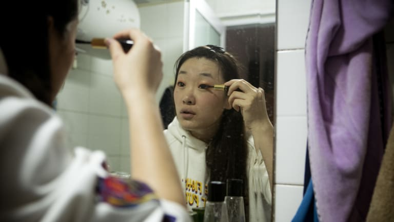 Shen Yue gets ready for her job at Chainfin.com where she also organises birthday parties and office competitions.