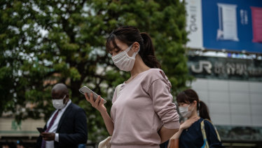 People wearing face masks wait to walk over Shibuya crossing in Tokyo, Japan.