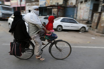 A Muslim family cycles home in Prayagraj, India.