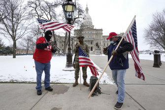 Protesters stand peacefully outside the state capitol in Lansing, Michigan during the inauguration.