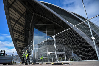 Workmen erect fencing around Glasgow's Scottish Exhibition & Conference Centre as it is turned into a field hospital.