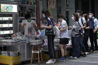 People queue to buy copies of Apple Daily in Hong Kong on Tuesday morning.