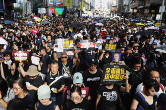 Demonstrators holding signs march along Hennessy Road during a protest in the Causeway Bay district of Hong Kong, earlier on Sunday.