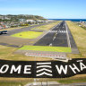 A giant sign painted near the main runway of the Wellington International Airport greets travellers returning home in Wellington.
