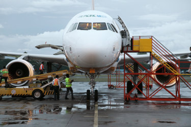 Puerto Princesa, Philippines - February 14, 2012: Workers supply plane before take-off iStock image for Traveller. Re-use permitted. Philippine Airlines