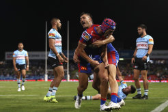 Knights star Kalyn Ponga (headgear) celebrates a try on Friday night.