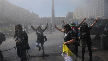 Anti-government protesters gleefully accept showers of water from a police water cannon that is meant to disperse them, outside La Moneda presidential palace in Santiago.