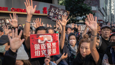 Demonstrators raise their hands on Hennessy Road in the Causeway Bay district of Hong Kong.