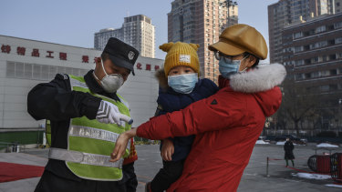 A woman has her temperature checked before entering a park with her child  in Beijing.