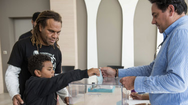 A boy helps his father to vote in New Caledonia's second independence referendum.