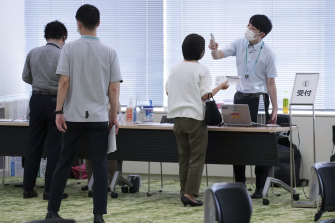 Employees of the beverage maker Suntory register to receive shots of the Moderna COVID-19 vaccine at their office in Tokyo.