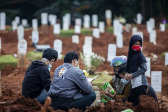Relatives visit the grave of a COVID-19 victim in Jakarta.