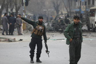 Afghan security personnel inspect the site of a bomb attack in Kabul, Afghanistan, Saturday, Dec. 26, 2020.