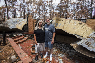 Liz and Nigel Girvan in the ruins of their Mallacoota home. There is no time frame to start the rebuild.