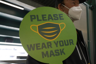 A stadium worker holds up a sign for people to wear face masks before a baseball game in California.