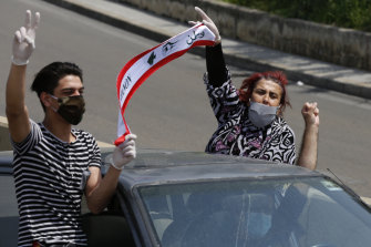 Anti-government protesters drive in a convoy through the streets of Beirut.