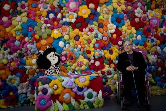 Quino poses next to his character at The World According to Mafalda exhibition in Buenos Aires, in 2014.
