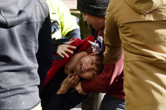 An anti-democracy protester grabs a man with a Taiwanese man around the neck at a rally in Sydney.