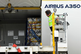 The first shipment of Pfizer COVID-19 vaccines is unloaded from a Singapore Airlines plane at Sydney International Airport on Monday.