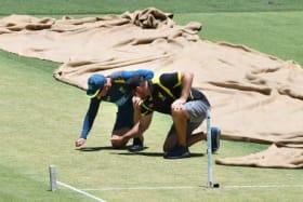 Australian coach Justin Langer and Optus Stadium curator Brett Sipthorpe inspect the pitch.