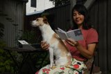 Illustrator Kim Siew looks back at one her many zines. She's pictured with her dog, Alfie.