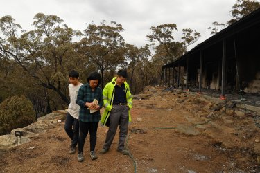 Balmoral residents Gabriel stands with his parents Helena and Justin in the days after their Balmoral home was destroyed by the Green Wattle Creek fire in December 2019.