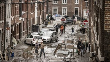 People walk through a damaged street after flooding in Chenee, in Belgium.