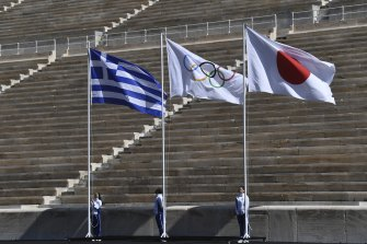 Athletes stand under the Greek, Olympic and Japanese flags during the Olympic flame handover ceremony for the Tokyo Summer Olympics in Athens in  March 2020.