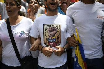 "A man wearing a shirt that reads in Spanish ""Venezuela. Strength and faith."" links arms with others at an opposition rally in Caracas on Tuesday."