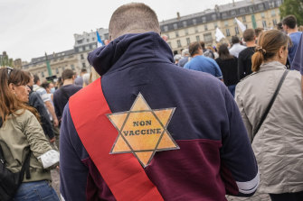 """A star that reads """"not vaccinated"""" is attached to the back of an anti-vaccine protester during a rally in Paris on Saturday."""