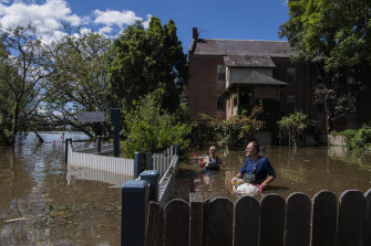 John and Sue Brookes cleaning up floating debris in the backyard of their Thompson Square home in Windsor.