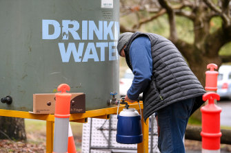 A resident of Kallista fills up a container with water brought in by Yarra Valley Water on Wednesday.