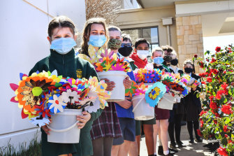 Students from several schools in Melbourne's east deliver paper flowers to residents of Arcare Knox.