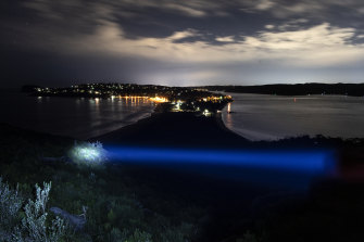 A blue torchlight beam  shines over the view of Palm Beach looking south from the lighthouse.