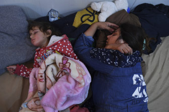 A woman and her child sleep in an Iraqi receiving area for refugees at Sehelan, on the Iraq-Syria border.