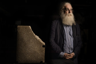Irving Finkel at the Nicholson Museum with an inscribed tablet on loan from the Australian Institute of Archaeology.