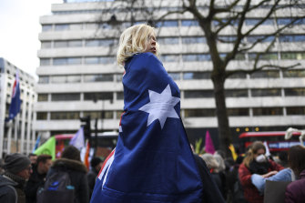 A young child wrapped in an Australian flag listens to speakers at the protest.